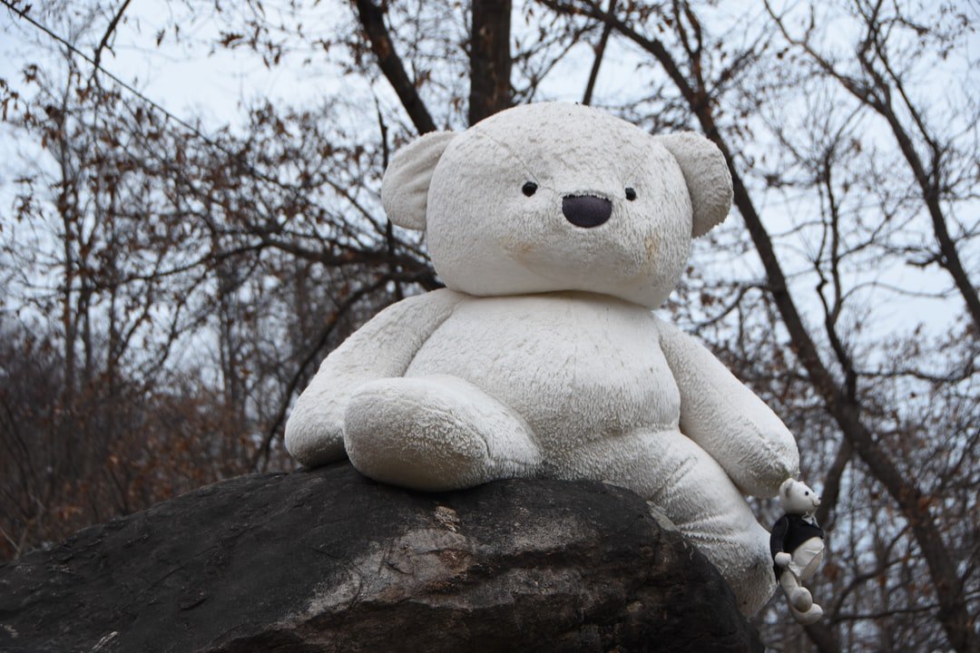 A large teddy bear standing next to a tree