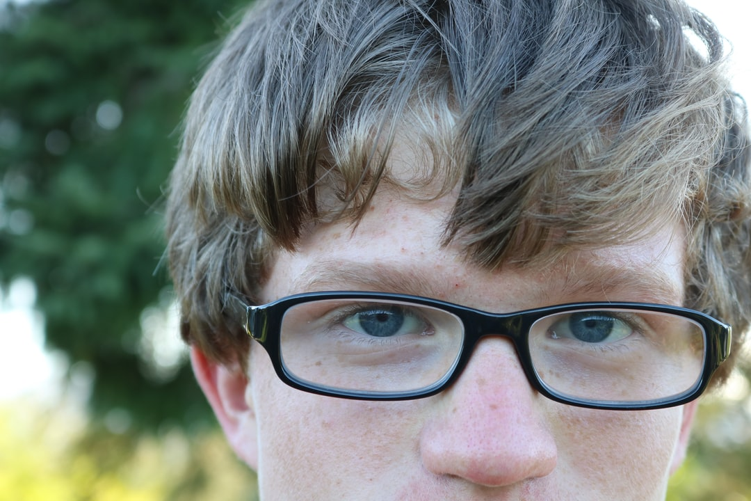 A close up of a person wearing glasses and looking at the camera